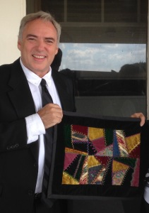 Eric Elder holding a quilt made by Marge Albrecht
